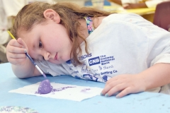 Ann Reese, 7, starts with a coat of purple paint.