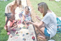 Jenny Johnson, project leader, helps kindergarteners place rocks.