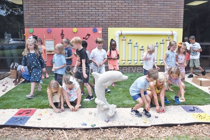 Kindergarteners place rocks in the garden on opening day June 5.