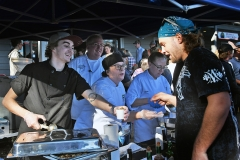 Greg Chestnut, Chef Bill Twaler, Deb Green, and Carole Penagos, of the International Culinary Institute of Myrtle Beach, serve their chicken bog to eager crowds of people.
