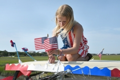 Addison GIllespie, 10, attaches flags to her grandfather's golf cart before the parade.