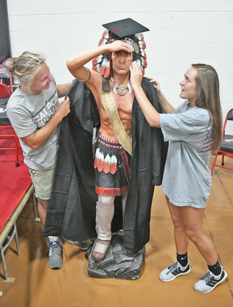 Peyton Brown and Ava Markam dress the warrior statue for graduation during rehearsal.