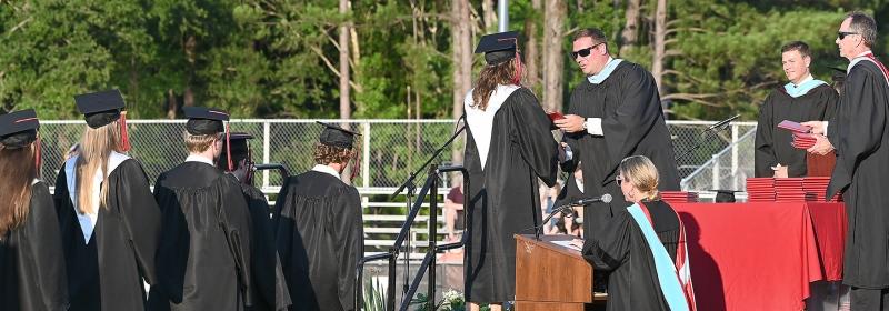 Principal Adam George hands out diplomas.