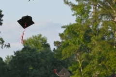 Graduates send mortarboards flying.